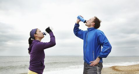 Couple drinking after exercise on beach